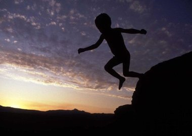Chris Steele-Perkins - A young bushman child leaps off a rock in Kaga Kama.