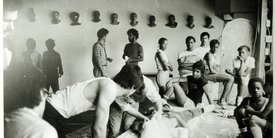 John Ahearn and Rigoberto Torres casting at Fashion Moda in 1979, with an audience of artists and neighborhood kids. Photo by Christoph Kohlhofer