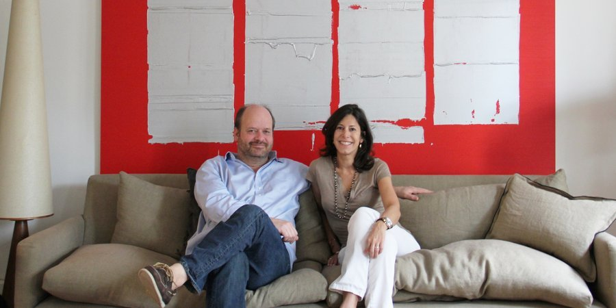 Alon and Betsy Kasha at home with a painting by John Zinsser