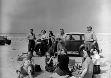 George Rodger - Total Eclipse of the Sun. Kuwaiti Oil Company personel and their families bring a picnic lunch to the desert to watch the eclipse. 1952.