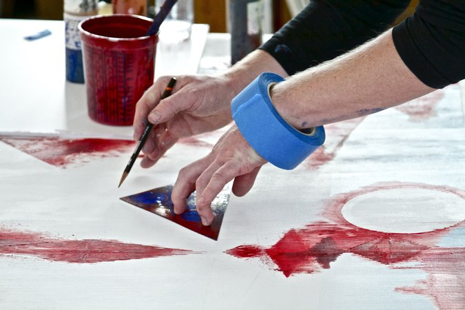 hands with blue tape red painting