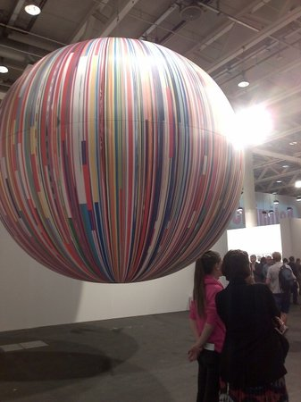 Resembling a planet orbiting around a star, Meschac Gaba's Citoyen du Monde: balloon (2013) partly eclipses one of the exhibition center's industrial lights.