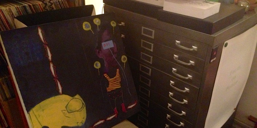 An exquisite corpse painting next to a flat file storage for unhung works on paper.