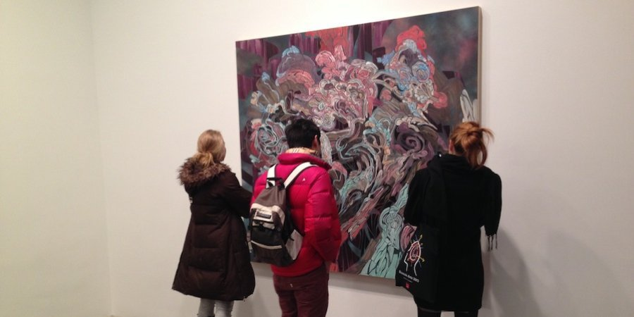 Viewers admiring an Emilio Perez painting