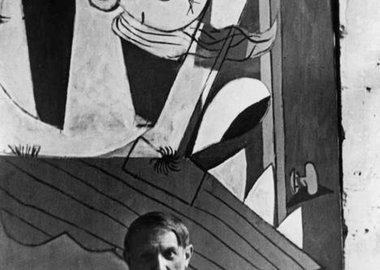 "David Seymour - Spanish painter Pablo Picasso in front of his painting ""Guernica"", at its unveiling at the Spanish Pavilion of the International World Fair held six weeks after the aerial bombing of the Basque village of Guernica."
