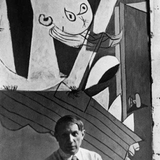 "Spanish painter Pablo Picasso in front of his painting ""Guernica"", at its unveiling at the Spanish Pavilion of the International World Fair held six weeks after the aerial bombing of the Basque village of Guernica. art for sale"